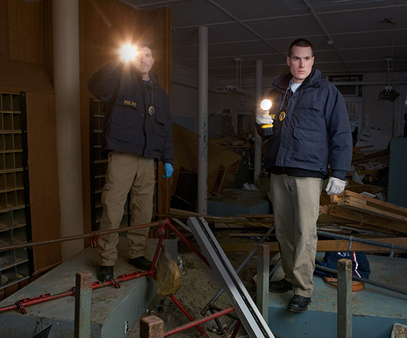 Two US Postal Inspectors shining flashlights